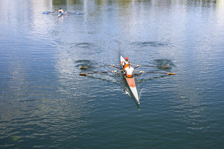 rower: Two Women Rower in a boat, rowing on the tranquil lake Stock Photo