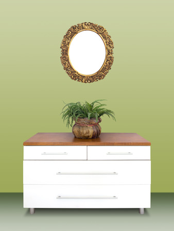chest of drawers: Modern white wooden chest of drawers and Antique gilded Frame on a green wall Stock Photo