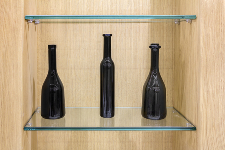 three shelves: Three Empty black bottles on a glass shelves in a wooden cabinet Stock Photo