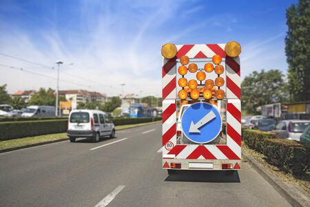roadworks: Road maintenance car signals detour due to roadworks Stock Photo