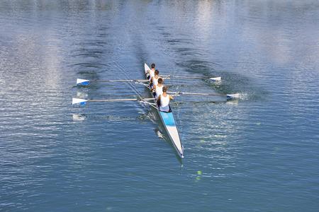 hilera: Remeros en botes de remos cuatro remos en el lago tranquilo
