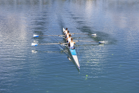sport team: Roeiers in vier-oar roeiboten op het rustige meer