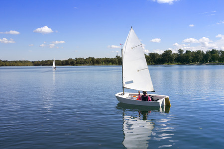 Small white boat sailing on the lake on a beautiful sunny day
