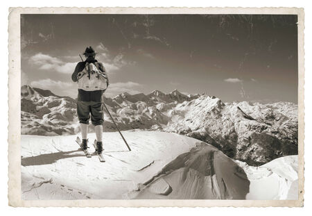 Vintage photo with old skier with traditional old wooden skis photo