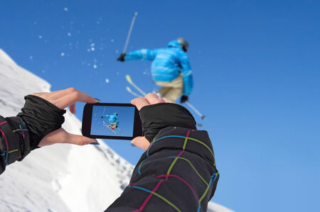 A young girl by mobile phone photographed of skiers jump Stockfoto