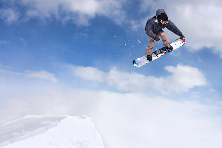 sport: Jumping snowboarder through air on blue sky background