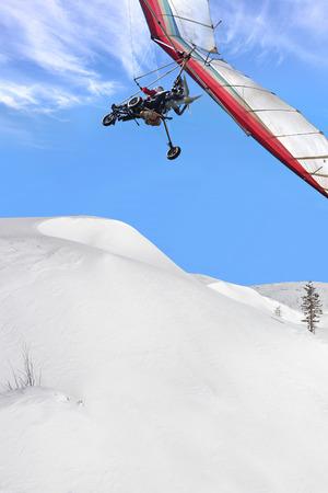motorizado: El ala delta motorizada cubierta de nieve por encima de la montaña del invierno