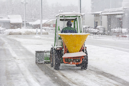 Small snowplow removing snow from sidewalk and sprinkled salt antifreeze Stock Photo - 34987603