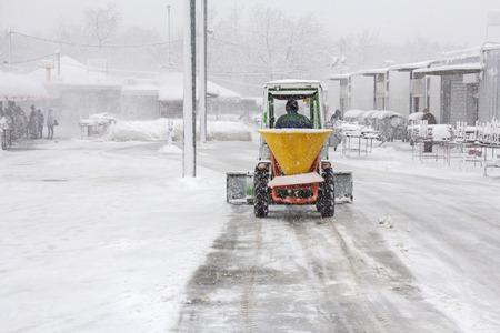 Kleine Schneepflug Schneeräumung von Bürgersteig und streute Salz Frostschutzmittel