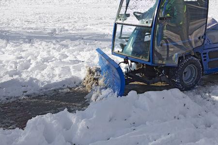 antifreeze: Blue snowplow removing snow from sidewalk and sprinkled salt antifreeze