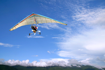 gliding: The motorized hang glider in the blue sky