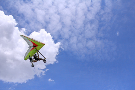 paraglide: The motorized hang glider flying in the blue sky Stock Photo