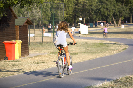 bike trail: A young woman riding a bicycle on the bike trail in the park Stock Photo