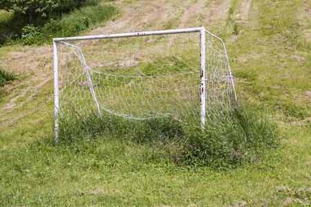 Neglected soccer goall on an uncut grass photo