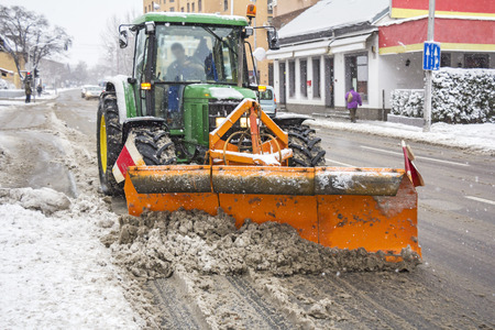 Snowplow tractor removing snow from city road photo