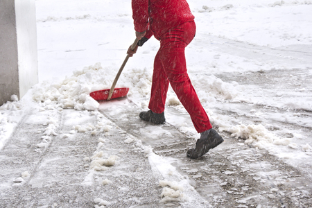 Worker in red uniform removes snow with red shovel