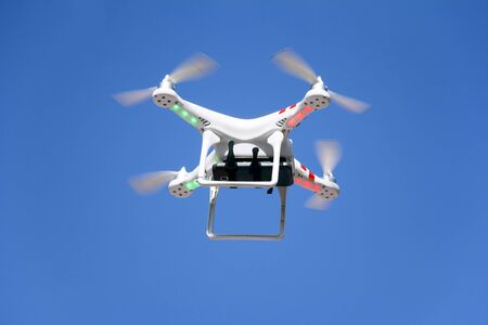 controlled: Radio controlled quadcopter drone flying in the blue sky Stock Photo