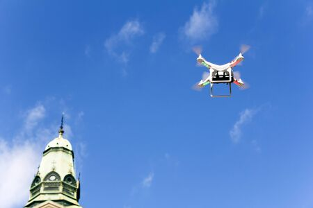 controlled: Radio controlled quadcopter drone flying over the city