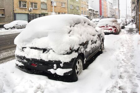 Cars parked on the street covered with fresh snow photo