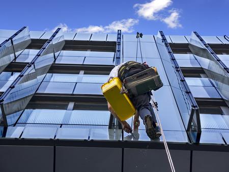 クライマー洗浄の窓と高層ビルのガラスのファサード 写真素材