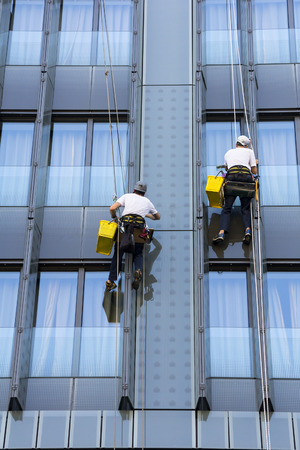 Two climbers wash windows and glass facade of the skyscraper