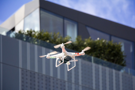 Radio controlled quadcopter drone flying in the city