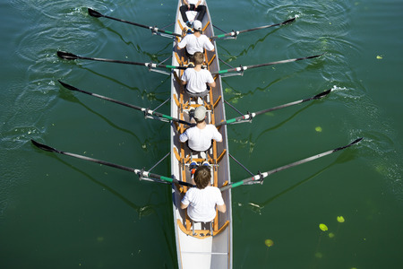 Boat coxed four team rowing on the tranquil lake photo