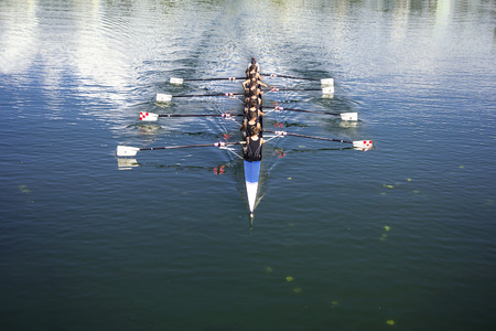 teams: Boat coxed eight Rowers rowing on the tranquil lake