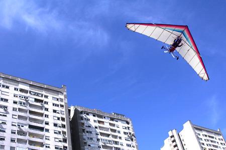 motorizado: El motorizado ala delta volando sobre los edificios residenciales en la ciudad Foto de archivo