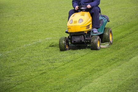 mower: Mowing the grass motor lawn mower on a football field
