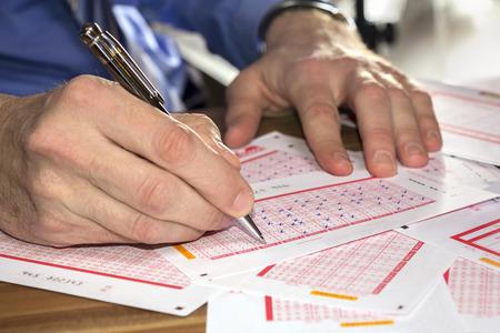 loteria: Hombre Marcado en el boleto de lotería con un lápiz
