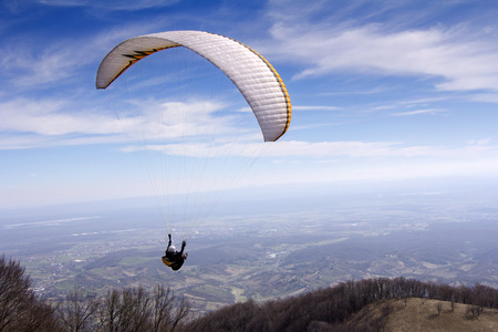 Paraglider flying over mountains to the valley photo