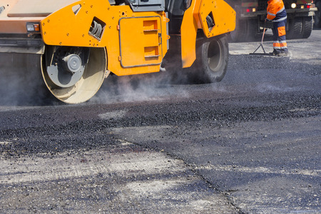 patching: Roller and workers on asphalting and repair of city streets