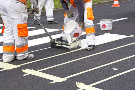 Two workers making of a new pedestrian crossing on the road