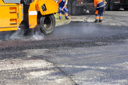 asphalting: Roller and workers on asphalting and repair of city streets