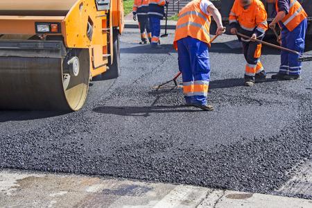 Roller und Arbeiter auf Asphaltierung und Reparatur von Straßen der Stadt