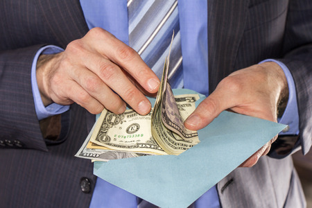 Businessman counting dollars bribe in a blue envelope