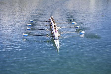 fila: Barco Coxed ocho remeros remo en el lago azul
