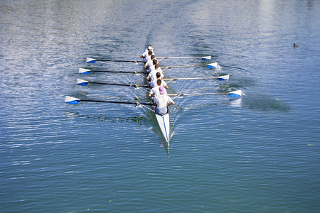 sport team: Boat coxed eight Rowers rowing on the blue lake