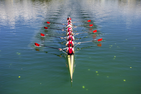 teams: Boat coxed eight Rowers rowing on the blue lake