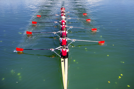 Bateau avec barreur huit rameurs d'aviron sur le lac bleu Banque d'images