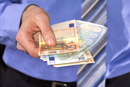 ブルーのシャツを着た男は、紙幣をユーロで支払う