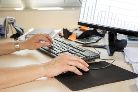using the computer: Mujer de negocios que trabaja en el ordenador en la oficina