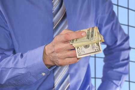 prostitution: Man in a blue shirt, is paying in dollars banknotes Stock Photo