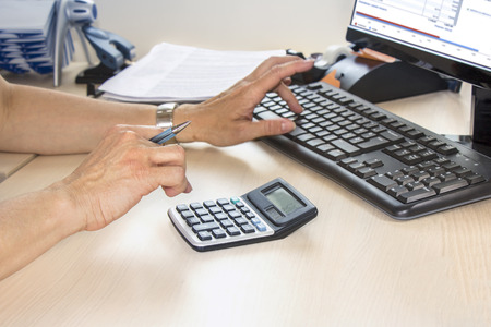 counting: Business woman typing on calculator in the office Stock Photo