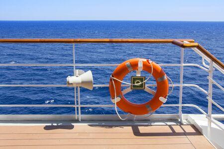 life buoy: Orange Life buoy on the deck of a cruise ship. Stock Photo