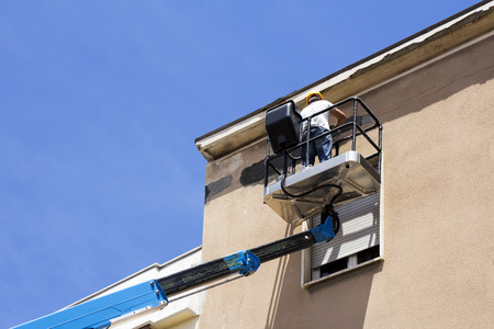 Manual worker on lift bucket repairs the buildings facade Stockfoto