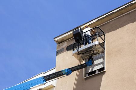 Manual worker on lift bucket repairs the buildings facade Standard-Bild