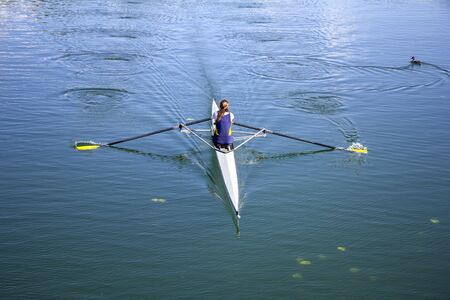 Young girl rower training rowing on the lake, to her wild duck