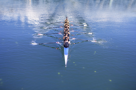 row: Rowers in eight-oar rowing boats on the tranquil lake